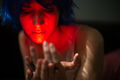 Young woman in red light, portrait - p1321m2181599 by Gordon Spooner