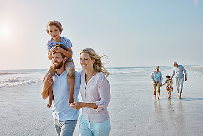 Happy extended family strolling on the beach - p300m1450203 by Roger Richter