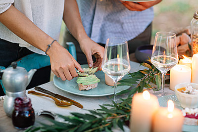 Close-up of couple preparing a romantic candelight meal outdoors - p300m2068343 by Alberto Bogo