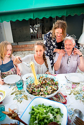Family having meal outdoors - p312m1107521f by Lena Granefelt