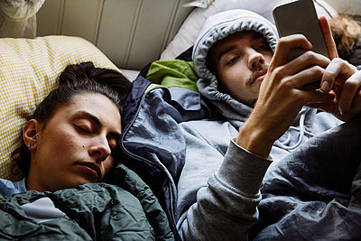 High angle view of young man using mobile phone while lying by friend on bed at home - p426m2117133 by Maskot
