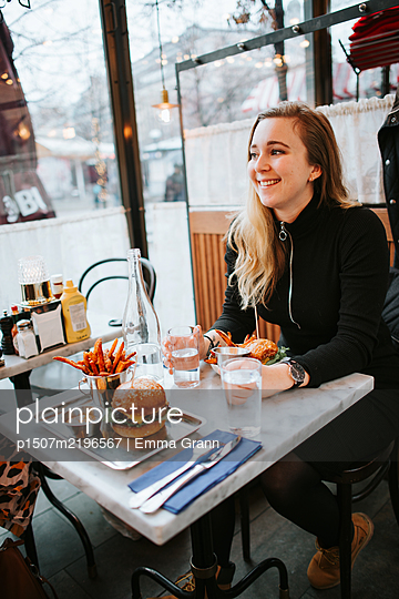 Young woman sits in fast food restaurant - p1507m2196567 by Emma Grann