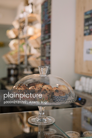 Cakestand with muffins on counter in a cafe - p300m2131722 by Alberto Bogo