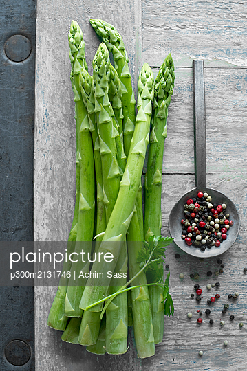 Green asparagus and pepper on wooden table seen from above - p300m2131746 by Achim Sass
