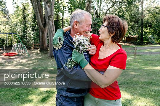 Affectionate senior couple embracing in backyard - p300m2276099 by Oxana Guryanova