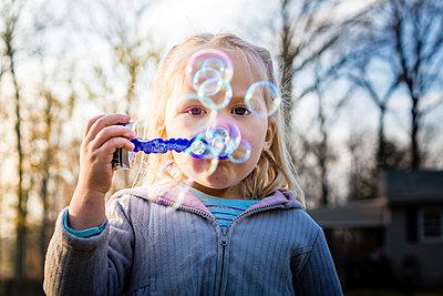 Portrait of girl blowing bubbles at backyard - p1166m1543327 by Cavan Social