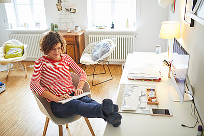 Mature woman sitting with feet up at desk at home using cordless keyboard - p300m1587258 von Philipp Nemenz