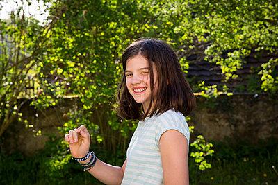 Portrait of laughing girl in the garden - p300m1588002 von Larissa Veronesi