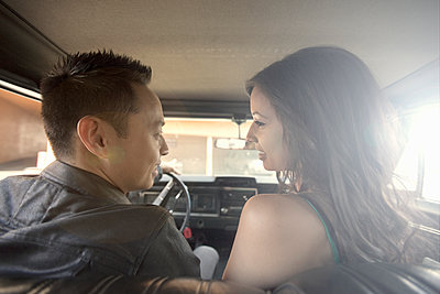 Young man and woman (23-30) chatting in car, Los Angeles, USA - p300m2264569 von LOUIS CHRISTIAN