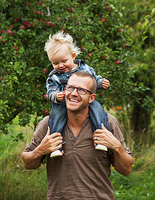 Father picking apples with his young son - p312m670276f by Matilda Lindeblad