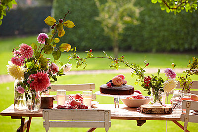 Late Summer picnic in garden with cakes  fruit and flowers - p349m2167896 by Sussie Bell