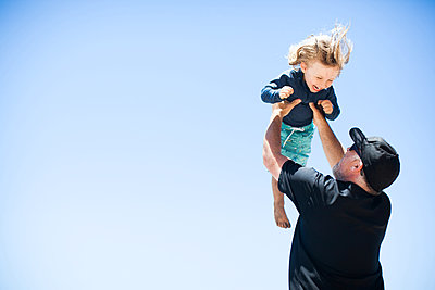 Father and son fooling around outdoors, father lifting son in air - p924m1422661 by Sasha Gulish