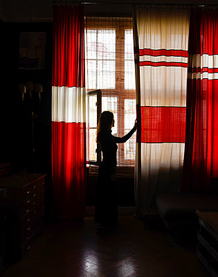 Woman looks out of window, Stay at home 2020 - p1190m2222469 by Sarah Eick