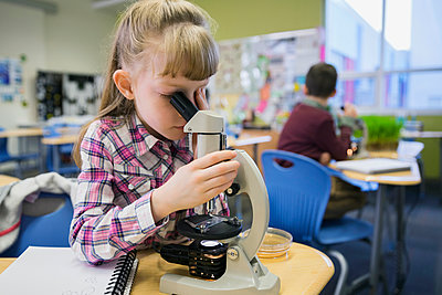Elementary student using microscope in laboratory - p1192m1016774f by Hero Images