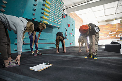 Female instructor and girl rock climber students stretching, preparing at climbing wall in climbing gym - p1192m1560056 by Hero Images