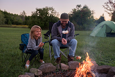 Father and daughter sitting beside campfire, toasting marshmallows over fire - p924m1197496 by Kymberlie Dozois Photography