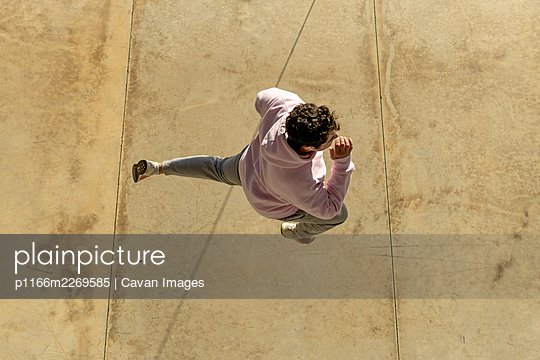shot from above of fat man jumping with sportswear - p1166m2269585 by Cavan Images