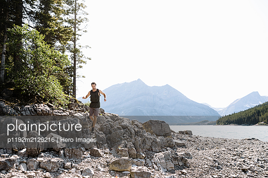 Man running over rocks at sunny lakeside - p1192m2129216 by Hero Images