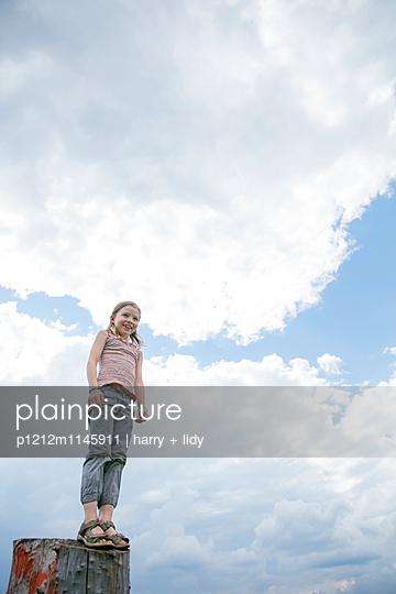 Mädchen steht auf Baumstumpf - p1212m1145911 von harry + lidy