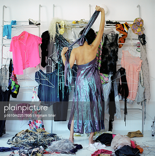 A woman trying some clothes on - p1610m2257895 by myriam tirler