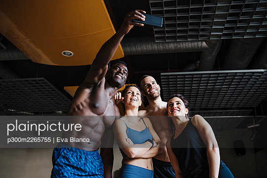 Smiling male and female athletes taking selfie through smart phone in health club - p300m2265755 by Eva Blanco