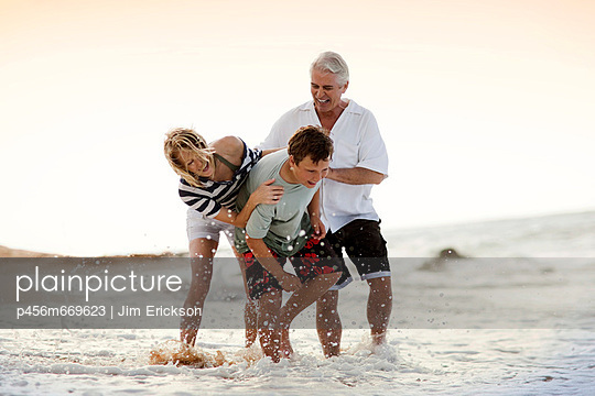 Family being silly on the beach together. - p456m669623 by Jim Erickson