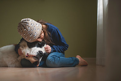 Girl stroking Saint Bernard while sitting at home - p1166m1414635 by Cavan Images