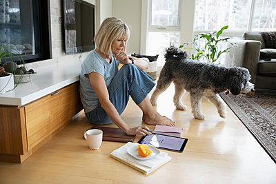 Woman with dog working from home, using digital tablet on living room floor - p1192m2088357 by Hero Images