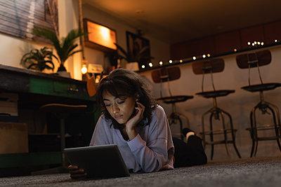 Woman using digital tablet on floor at home - p1315m2062696 by Wavebreak