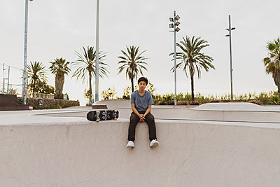 Young Chinese man sitting on wall of a skate park near the beach - p300m2012289 von VITTA GALLERY