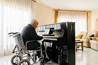 Senior man sitting in wheelchair playing piano at home - p300m2160574 von Josep Rovirosa