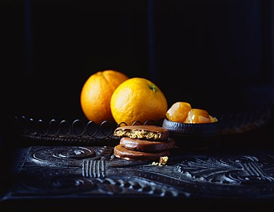 Luxury chocolate coated orange flavoured biscuits and oranges on vintage table, low key - p429m1106803f by Diana Miller