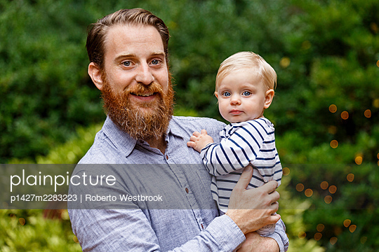 Portrait of father holding baby girl, outdoors, smiling - p1427m2283223 by Roberto Westbrook