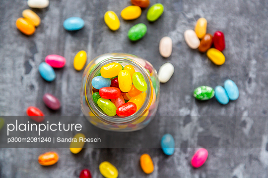 Glass of colourful sweet jellybeans on gray background - p300m2081240 by Sandra Roesch