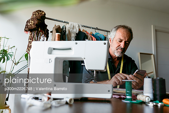 Mature male tailor using smart phone while sitting at table in work studio - p300m2226748 by Valentina Barreto
