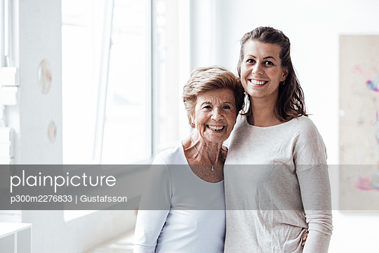 Smiling senior woman embracing granddaughter at home - p300m2276833 by Gustafsson