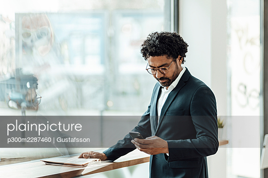 Male entrepreneur using smart phone while standing by glass window in office - p300m2287460 by Gustafsson
