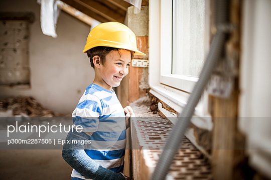 8 year old boy with broken arm on construction site in attic or loft during renovation with yellow safety helmet, austria - p300m2287506 von Epiximages