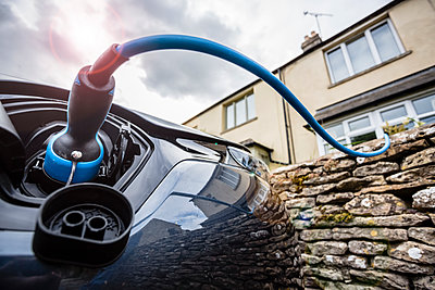 An elctric car and charging point, parked on the side of the road outsiude a house with blue cable. - p1057m1463583 by Stephen Shepherd