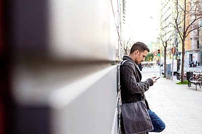 Side view of a bearded man using phone leaning on office building wall - p1166m2190511 by Cavan Images