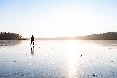 Germany, Brandenburg, Lake Straussee, frozen lake and silhouette of an ice skater - p300m1580978 by Julia Otto