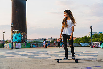 Young woman riding skateboard in the city - p300m2060993 by Kike Arnaiz