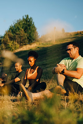 Male and female athletes meditating while sitting on grass in park during sunny day - p426m2270782 by Maskot