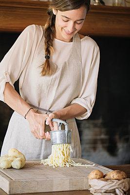 Woman using potato ricer to prepare gnocchi - p429m2035654 by Alberto Bogo