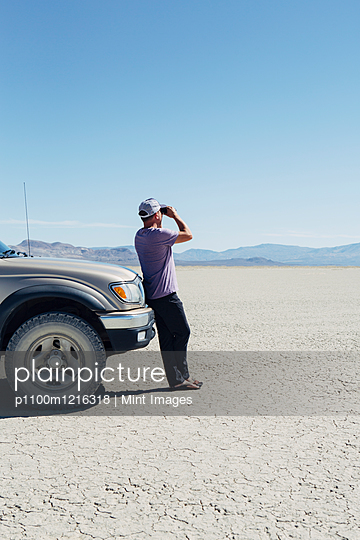 Man standing on vast desert, looking through binoculars and leaning against truck, Black Rock Desert