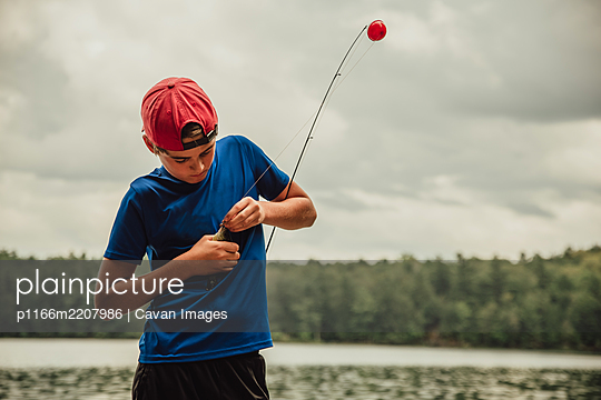 Close up of teen boy with a fish on his rod on a lake in the summer. - p1166m2207986 by Cavan Images