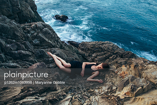 Women Laying on Rocky Shore - p1262m1063998 by Maryanne Gobble