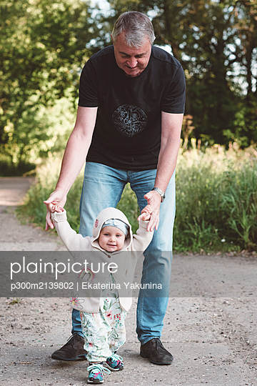 Little girl making her first steps with her grandfather - p300m2139802 by Ekaterina Yakunina