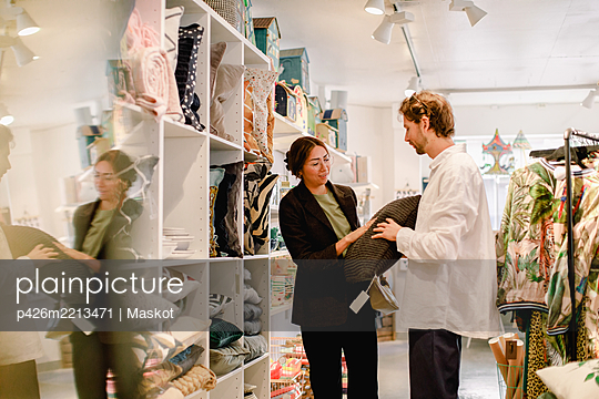 Man and woman looking at cushion in retail store - p426m2213471 by Maskot
