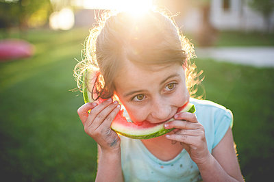 Girl eating watermelon while sitting on grassy field - p1166m1230468 by Cavan Images